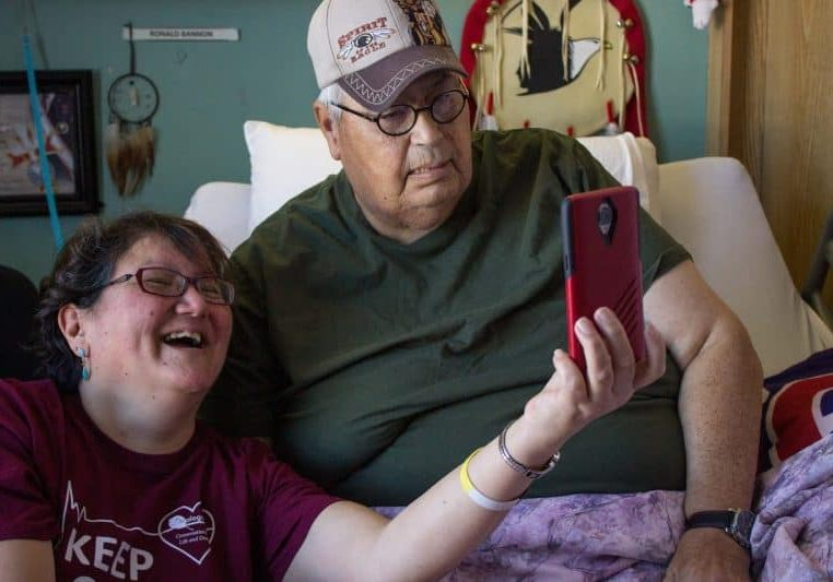 Indigenous man and volunteer Facetiming with family